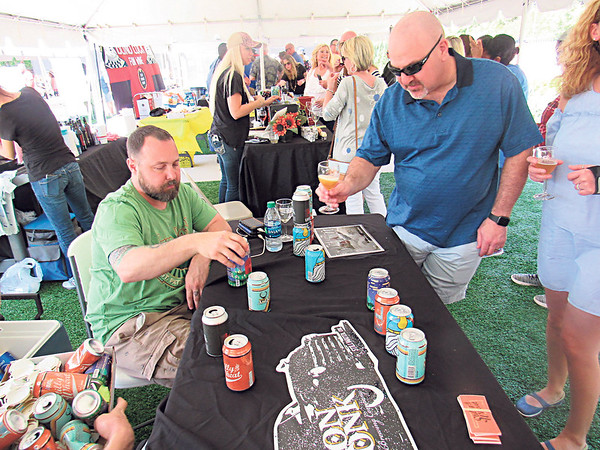 CATHY SPAULDING/Muskogee Phoenix<br /> Matt Sullins of Iron Monk Brewery, left, shows Andrew Olshen the variety of beers at Iron Monk's Party in the Park booth. The party attracted hundreds of beer and wine lovers.