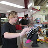 CATHY SPAULDING/Muskogee Phoenix<br /> Toby's Pit Stop employee Paige Staton wipes a credit card scanner at the convenience store's counter. A plexiglass barrier separates a customer from people behind the counter.
