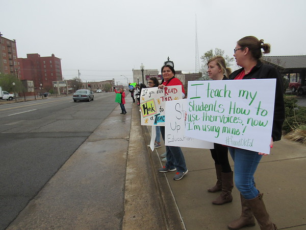 CATHY SPAULDING/Muskogee Phoenix<br /> Muskogee Public Schools teachers, from left, Anita Custer of Ben Franklin Science Academy, Sandy Cason of Whittier Elementary and Klaire Starkey of Whittier hold up signs soliciting support for education while standing in front of Muskogee Civic Center on Monday.