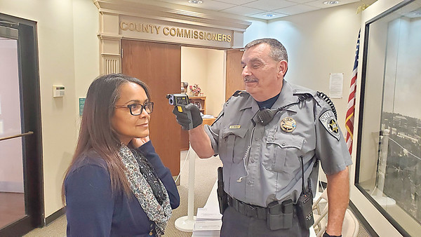 CHESLEY OXENDINE/Muskogee Phoenix<br /> Sharlene Hill has her temperature taken by Danny Belbot as she enters the Muskogee County Services Building.