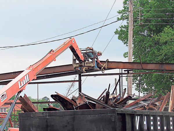 CATHY SPAULDING/Muskogee Phoenix<br /> A worker with Bowden Steel Buildings reaches to hook a belt around a steel frame onto a forklift Monday. The company is demolishing a<br /> former auto repair shop on North Seventh Street. The building, formerly Fast Wrecker, was destroyed in a 2015 fire.