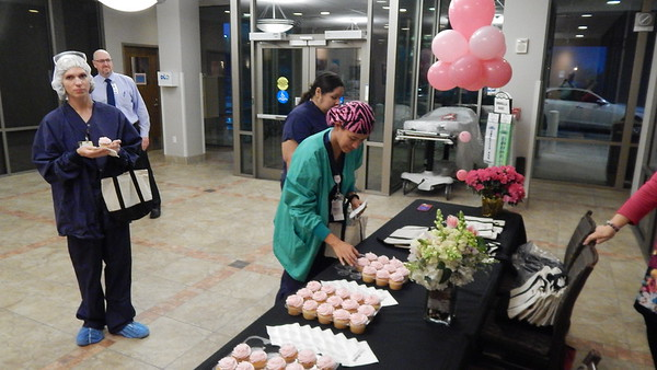 Staff photo by Mark Hughes<br /> Krysten Foreman, certified surgical technician, takes a pink cupcake Monday morning that was part of celebrating EASTAR Health System becoming Saint Francis Hospital Muskogee. Promotional bags also were available to employees.