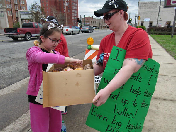 CATHY SPAULDING/Muskogee Phoenix<br /> Whittier Elementary teacher Melissa Jackson offers a doughnut to her 12-year-old daughter, Piper Jackson, while holding signs in front of Muskogee Civic Center on Tuesday.