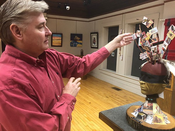 "CHESLEY OXENDINE/Muskogee Phoenix<br /> Five Civilized Tribes Museum Director Sean Barney discusses D.L. Corley's ""The Greatest Identity Theft,"" a sculpture featured in the annual Art Under the Oaks competitive art show."
