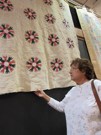 Staff photo by Cathy Spaulding<br /> Muskogee Area Quilt Guild chairwoman Pegge Condren admires a 150-year-old quilt.