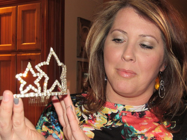 Staff photo by Cathy Spaulding<br /> Kara Mitchell admires a crown she wore in an Azalea Festival Parade. Mitchell, the 1994 Azalea Queen, rode with past queens in 2009 and will ride again on Saturday.