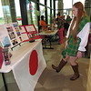 Staff photo by Cathy Spaulding<br /> Connors State College nursing student Brittanie Hulbert, dressed in Irish garb, studies a booth about Japan during CSC's International Day Wednesday. The event was marked at the Port campus and Warner campus.