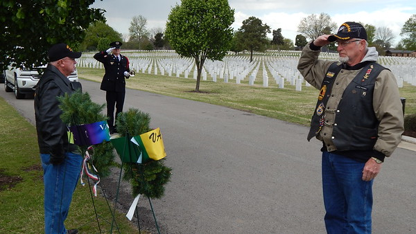 Staff photo by Mark Hughes<br /> Clark Donnell salutes after placing the last of two wreaths at a commemoration ceremony Wednesday afternoon at the Fort Gibson National Cemetery. Mike Pennington stands by the wreath he laid. The ceremony honored veterans who served in World War I. April 6 is the 100th anniversary of the United States entering World War I in 1917. Last week was when the United States officially withdrew from the Vietnam War, which was also part of the commemoration. Donnell and Pennington are Vietnam War veterans.