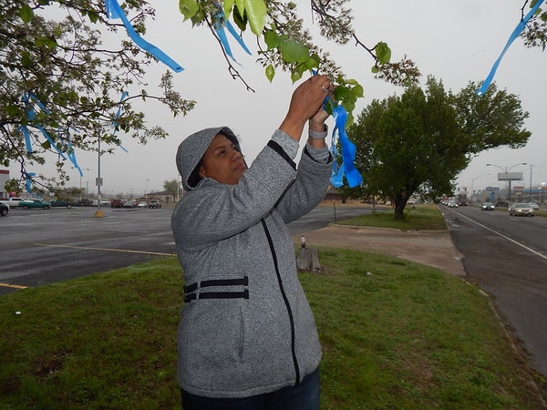 KENTON BROOKS/Muskogee Phoenix<br /> Mariah Crutcher, a child welfare specialist for the Muskogee County Department of Human Services, ties a blue ribbon to a tree to bring attention to child abuse awareness.