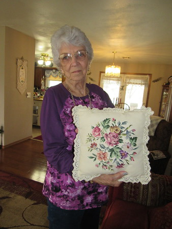 Flowers accent a needlepoint pillow Mildred Ewing made.