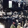 Staff photo by Wendy Burton<br /> Firefighters move debris as an investigation begins into the cause of a house fire on South 14th Street early Friday morning, which completely destroyed the home of a Muskogee woman and three others.