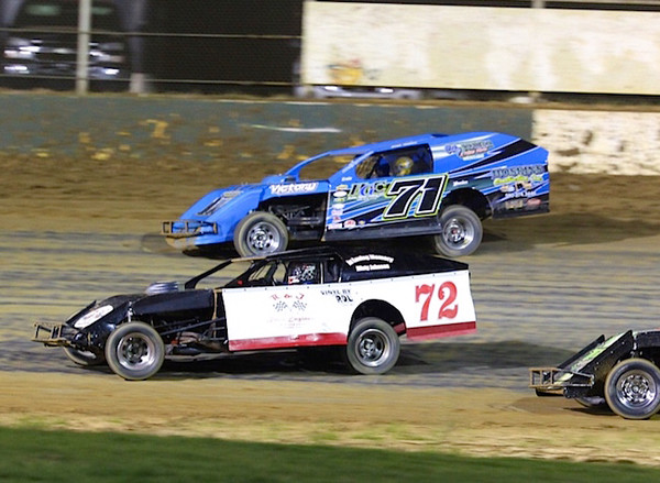 Special photo by Darren Stephens<br /> NASCAR legend Kenny Wallace, back, tries to pass Muskogee's Shannon Reheard heading into Turn 3 during Wednesday's IMCA Modified A feature at Outlaw Motor Speedway. Wallace will start his final NASCAR race today in the Xfinity series race at Iowa Speedway.