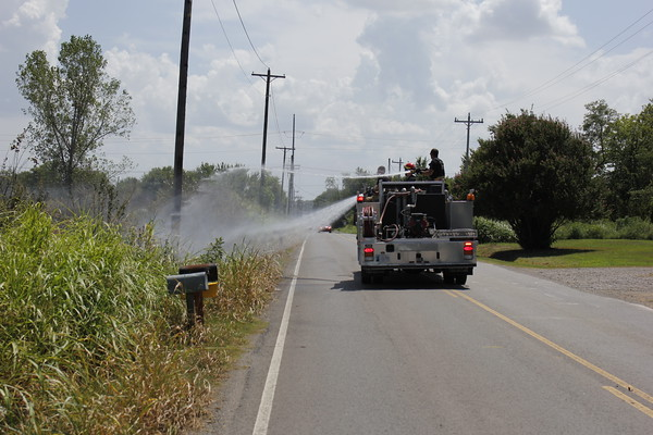 Staff photo by Harrison Grimwood<br /> Muskogee firefighters respond Tuesday afternoon to one of three separate grass fires in the 2600 block of North Main Street. Muskogee Fire Department Capt. Aaron Mayhugh said the fires did not have a readily apparent cause. No one was injured.