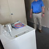 Staff photo by Cathy Spaulding<br /> Rich Schaus, the executive director of Gospel Rescue Mission, shows its new washing machine, donated by Muskogee Church of Christ, which will help the mission provide decent, clean clothes for men. Church volunteers cleared space for a men's clothing area.