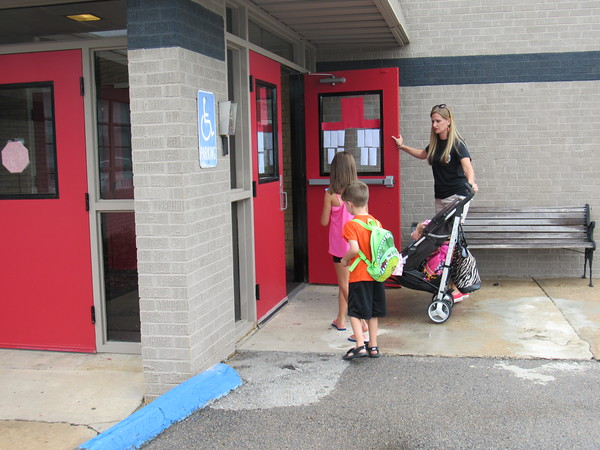 Staff photo by Cathy Spaulding<br /> Hilldale parent Emily Cope holds the Hilldale Upper Elementary front door open for her children Natalee, 7, Jaxon, 4, and Brooklin, 1. A bond issue set for an Aug. 23 vote would fund a new entrance linking Hilldale Upper Elementary and Lower Elementary.