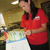 Staff photo by Cathy Spaulding<br /> Hilldale Middle School teacher Sara Hyde looks through a math textbook with students' names dating back 11 years. A $13.4 million bond issue includes funding for updated textbooks.