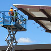 Staff photo by Cathy Spaulding<br /> Workers stand on a high lift as they work on an awning at The Outpost gas station and convenience store. The Outpost remodeling is one of several projects under way at the Cherokee Nation tribal complex south of Tahlequah.