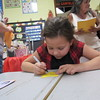 Staff photo by Cathy Spaulding<br /> Whittier Elementary second-grader Aaliyah Strickland writes her name on a star during a Back to School gathering Tuesday. She placed the star at a desk she liked. Muskogee Public Schools had Back to School nights at each elementary school Tuesday. Classes at Whittier begin at 8:30 a.m. Thursday.