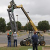Staff photo by Harrison Grimwood<br /> Contractors for the city install the first downtown gateways Wednesday morning at North Third and Denison streets. The two pillars feature bronze seals of the city, Warfeather contractor Adam Oglesbee said. The remaining gateways, including an arch and a freestanding arch, should be installed throughout the next six weeks, he said.