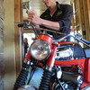 Staff photo by Cathy Spaulding<br /> Ghost Diaz of Ghost Mobile Detailing shines a mirror on a 1969 Yamaha Enduro. Attorney and restaurant owner Brian Berry donated the cycle for a drawing during Big Jim's Motorcycle Rally this weekend.