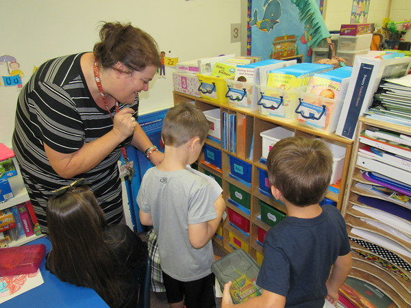 Staff photo by Cathy Spaulding<br /> Hilldale Elementary teacher Lisa Dotson shows students where to put their pencil boxes Thursday on the first day of school.