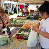 Special photo by Travis Sloat<br /> Yer Yang, with Beautiful Vegetables, bags lettuce and onions for Debbie Graham and her poodle, Mia, at the Tahlequah Farmers' Market. Graham said she likes coming to the market to get out of the house.