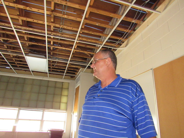Staff photo by Cathy Spaulding<br /> Porter School Superintendent Mark Fenton surveys damaged ceilings at Porter Middle School. The district has delayed the start of classes to Aug. 29.