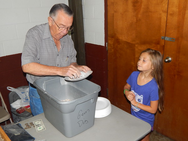 "Staff photo by Mark Hughes<br /> Emily Oglesbee, 7, looks with anticipation as Jerry Hudson pours out a scoop of pebbles from the ""gem dig"" bucket. Among the pebbles were chips from polished stones and minerals that children retrieved with tweezers."