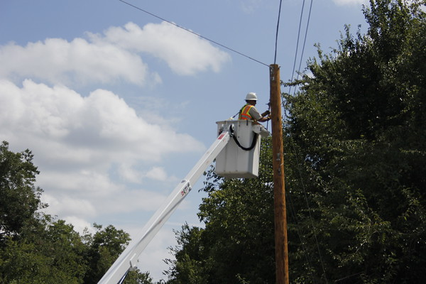Staff photo by Harrison Grimwood Suddenlink Demand Technician Ray Chapman wraps up transferring a communications line to a different utility pole Monday afternoon. The pole the line had previously been on had been hit by a car, he said.