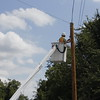Staff photo by Harrison Grimwood<br /> Suddenlink Demand Technician Ray Chapman wraps up transferring a communications line to a different utility pole Monday afternoon. The pole the line had previously been on had been hit by a car, he said.