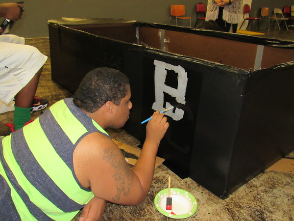 Staff photo by Cathy Spaulding Bacone freshman Anthony Eugene adds lettering to the cardboard craft.