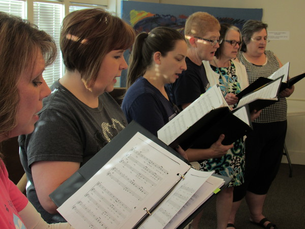 Staff photo by Cathy Spaulding Okiepella singers Peggy Harris, left, Laurie Havron, Meaghan McCawley, Kerry Huffer, Bert Luton, and Marsha Reynolds blend voices during rehearsal. Women and men in the a capella group will perform this weekend.