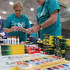 Staff photo by Cathy Spaulding<br /> Paula Christensen and Larry Christensen open eraser packets while sorting school supplies for a backpack giveaway. St. Paul United Methodist Church will distribute backpacks at a Sept. 11 community block party.