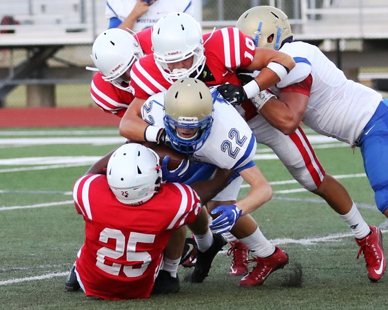 Special photo by John Hasler Sammy Sanchez, bottom, and Caden Abbott wrap up Oologah's Ty Dixon in Thursday's scrimmage at Fort Gibson.