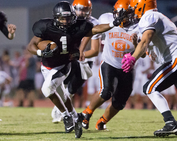 Sppecial photo by Von Castor Hilldale's Mikey Winston stiff-arms his way through the Tahlequah defense Thursday evening during a four team scrimmage which also included Wagoner and Rogers, Arkansas, hosted by Hilldale.