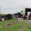 Staff photo by Cathy Spaulding<br /> Meat removed from an overturned tractor-trailer rig is loaded into another tractor-trailer Friday on the Muskogee Turnpike just north of Peak Boulevard. The driver was not injured.