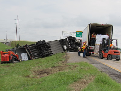 Staff photo by Cathy Spaulding Meat removed from an overturned tractor-trailer rig is loaded into another tractor-trailer Friday on the Muskogee Turnpike just north of Peak Boulevard. The driver was not injured.