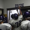 "Staff photo by Harrison Grimwood<br /> Vian Wolverines tap the ""Pride"" sign in their locker room as they head out for the practice field."