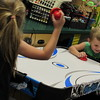 Staff photo by Cathy Spaulding<br /> Connor Lacey dodges a plastic puck while playing air hockey with Gemma Kolmer. Students have games and learning opportunities at Fort Gibson's before- and after-school program.