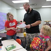Staff photo by Cathy Spaulding<br /> Fort Gibson before- and after-school program director Kim Gleissner, left, helps Gary Epperson with the program schedule, while his daughter Kadence, 7, waits. The program serves children from pre-kindergarten through fifth grade.