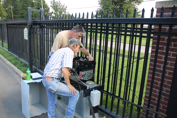 Staff photo by Harrison Grimwood<br /> Brent Webster, back, and Mark Miller, construction maintenance technicians for the Oklahoma School for the Blind, troubleshoot one of the school's automated exit gates Monday afternoon.