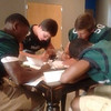 Staff photo by Mike Kays<br /> Quintahj Cherry, left, Hunter Watkins, Zane Rasmussen and Tavian Davis fill out questionnaires Monday as part of the first of the two Phoenix Prep Football Media Days this week held at Muskogee First Assembly of God.