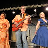 "Staff photo by Cathy Spaulding<br /> Jim Blair, center, plays Buddy Holly and Hank Williams tunes, backed by Elizabeth Escobar, left, and Angelina Cummings in the Muskogee Little Theatre production ""On With the Show, This Is It."" The production runs from Friday through Aug. 13."