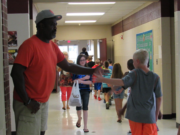Staff photo by Cathy Spaulding<br /> Central Intermediate School custodian Stevan Thomas greets students Thursday for the first day of Wagoner Public Schools' school year. Thomas has been a custodian for 17 years.
