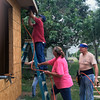 Special photo by Travis Sloat<br /> Barbara Kent holds a ladder and airgun hose for Tony LaBounty as Roy Entz stands by to do his part in the construction of her Habitat for Humanity home.