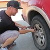 Staff photo by Cathy Spaulding<br /> Matt Young inflates a tire for a customer. Oil checks and tire checks are part of his work at the full-service gas station he owns.