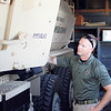 "Staff photo by Harrison Grimwood<br /> Muskogee Police Department spokesman Lincoln Anderson inspects the department's Mine-Resistant Ambush Protected vehicle in preparation for the ""Fill the Truck"" school supply drive this Friday."