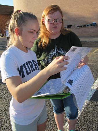 """Staff photo by Cathy Spaulding<br /> Fort Gibson High School seniors Reanna Nichols, left, and Shea Davis study the diagram for the Royal Regiment's 2016 field marching program, """"Nemesis."""" Band members practice the patterns early each morning."""
