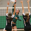Special photo by Von Castor<br /> Muskogee's Claire Farmer, center and the two-time All-Phoenix MVP, goes around the block of Owasso's Chanan Drake, left, and Tate Tieperman during a match last August in Muskogee. The Lady Roughers begin the 2015 season at 5 p.m. Tuesday against Bishop Kelley.