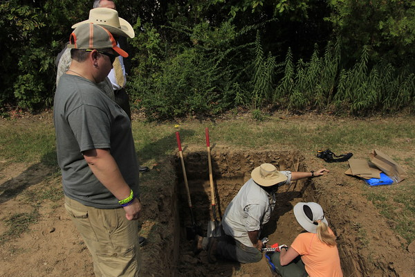 Staff photo by Harrison Grimwood<br /> Forensic anthropologists with the Office of the Chief Medical Examiner in Oklahoma gently scrape dirt away from an unmarked grave Tuesday, hoping to uncover the remains without damaging them.